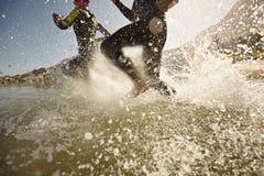 Triathlonteilnehmer, die in das Wasser für Schwimmenteil laufen lizenzfreie stockfotografie