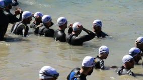 Triatlonagenten vóór het zwemmen in een meer stock videobeelden