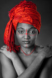 Tribal African woman with headwrap. Beautiful ethnic traditional African-American woman wearing a authentic tribal red orange head scarf and red dotted makeup Stock Photos