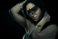 Tribal.Beautiful young woman in mysterious black Venetian mask. Royalty Free Stock Images