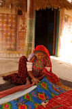 Tribal Culture. February 30, 2012 Kutch,Gujarat,India,Asia-An old Lambada woman sewing a cloth infront of her painted hut Stock Image