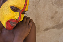Tribal face. Young African girl, tribal painted face in yellow and red Royalty Free Stock Images