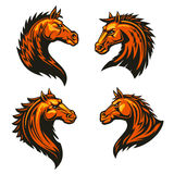 Tribal fire horse mascots with spiky brown mane. Tribal flaming horse head mascots of angry stallion horse with spiky brown coat and mane. Sporting team or club Royalty Free Stock Photography