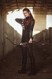 Tribal girl in leather costume with tight bowstring inside abandoned building Stock Photo