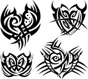 Tribal hearts and shields. Four tattoos with abstract hearts and shields Stock Image