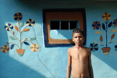 Tribal Life of India. June 02,2011 Rampurhut,Birbhum,West Bengal,India,Asia-A tribal boy standing infront of their traditional wall painting in the remote stock photo