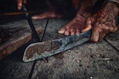 Tribal man sharpening his arrow for hunting at his jungle home. Muara Siberut, Mentawai Islands / Indonesia - Aug 15 2017: Tribal man sharpening his arrow for royalty free stock photos