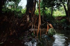 Tribal member lady fishing for small fry and shrimps in the jungle stre stock photos