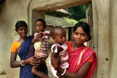 Tribal Mothers. Tribal women are standing in front of their house with their child in lap Stock Image