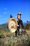 Tribal woman with horns playing a Buffalo drum on the mountain stock photos