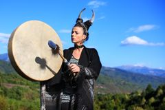Tribal woman with horns playing a Buffalo drum on the mountain royalty free stock images