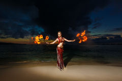 Tribal style girl on a tropical beach dancing with fire at sunse Royalty Free Stock Photo
