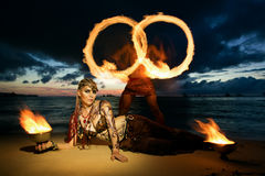 Tribal style girl on a tropical beach with fire at sunset. Stock Image