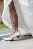 Tribal tatto on leg of a bride with white shoes an Royalty Free Stock Photo