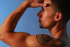 Tribal tattoo. Pensive hispanic male with tribal tattoo royalty free stock photos