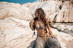 Tribal woman on the rocks royalty free stock photo