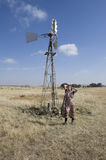 Tribal woman standing next to windpump on farm Stock Images