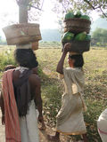 Tribal women carry goods  on their heads Royalty Free Stock Image