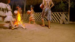 Tribe man and child playing drum. Indigenous playing musical instrument during traditional event in amazonian jungle at night in Ecuador stock video footage