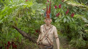 Tribe man walking in jungle. Caucasian adult man dressed up as indigenous during walking looking at camera in the jungle in Ecuador stock footage