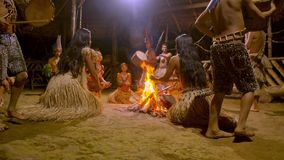 Tribe people dancing. Indigenous performing puja of fire and playing musical instrument traditional event in amazonian jungle at night in Ecuador stock video