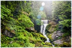 Inside the Schwarzwald Black Forest. Triberg Waterfalls, water cascades , Black Forest, Schwarzwald, Germany.Water cascades through the lens flare against the stock photo