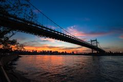 Triborough bridge over the river with sunset. Triborough bridge over the river in silhouette before sunset Royalty Free Stock Photos