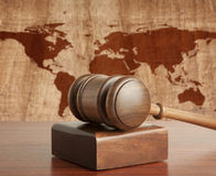 Tribunal. Wooden gavel on a background map of the world Stock Image