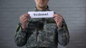 Tribunalwort herein geschrieben auf Hände des Zeichens des männlichen Soldaten, Militärgericht, Verbrechen stock footage
