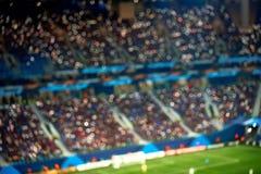Tribunas llenas del estadio de fútbol del fútbol con las luces Fondo borroso foco suave imágenes de archivo libres de regalías