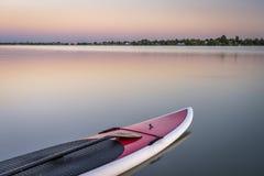 Tribune omhoog paddleboard op meer Stock Foto's