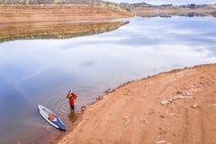 Tribune omhoog paddler op een meerkust royalty-vrije stock foto