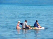 Tribune op het surfen van de Peddel Een familie berijdt een raad Stock Fotografie