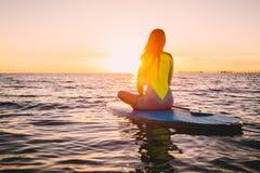 Tribune op peddel die op een stille overzees met de warme kleuren van de de zomerzonsondergang inschepen Het ontspannen op oceaan Stock Foto