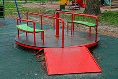 Tribunes van de het metaalcarrousel van kinderen de ronde gekleurde op de speelplaats stock foto's