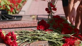 People putting carnation red flowers on granit steps by Eternal flame monument. stock footage