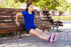 Tricep dips on a park bench stock image