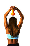 Tricep press orange. Woman doing a tricep press with a silver dumbbell stock images
