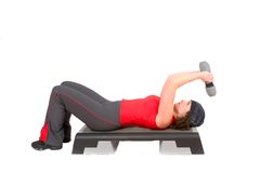 Triceps curls. Pretty woman doing triceps curls while lying on a step royalty free stock photo
