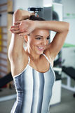 Triceps. Cute Sporty young woman doing exercise in a fitness center. She is working exercises to strengthen her triceps royalty free stock photography