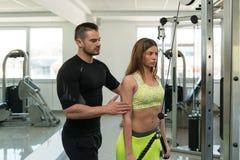 Triceps de train de femme sur la machine avec l'entraîneur personnel photos libres de droits