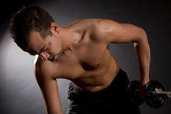 Triceps exercise. Handsome young man doing triceps exercises on black background royalty free stock photos