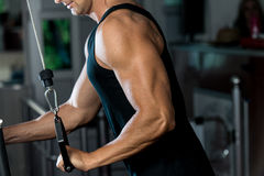 Triceps Pulldown Workout. Fit man on the triceps pulldown weight machine at a health club Stock Images