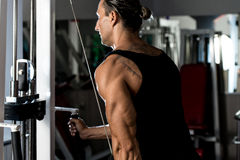 Triceps Pulldown Workout. Fit man on the triceps pulldown weight machine at a health club Royalty Free Stock Photography