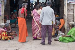 Beggars at an Indian holy place. Trichy, India - March 14, 2018: Beggars lining both sides of the entrance to the Amma Mandapa ghats where priests provide stock photos