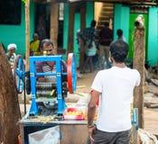 TRICHY, LA INDIA - 15 DE FEBRERO: Un hombre no identificado exprime el ju Imagen de archivo libre de regalías