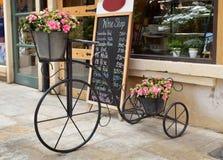 Triciclo antiguo y flores artificiales Foto de archivo