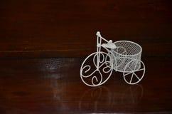 Triciclo branco para a decoração em cintilar o assoalho de madeira imagens de stock royalty free