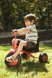 Triciclo del montar a caballo del muchacho. Foto de archivo libre de regalías
