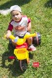 Triciclo del montar a caballo del muchacho del niño Imagen de archivo libre de regalías